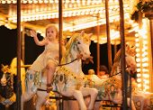 stock photo of carousel horse  - Portrait of happy baby girl riding on carousel