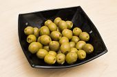 stock photo of marinade  - Marinaded olives in a black square plate - JPG