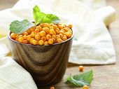 foto of sea-buckthorn  - fresh ripe organic sea buckthorn berries in a wooden mug - JPG