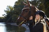 picture of fondling  - Riverside portrait of happy female rider and beautiful horse - JPG