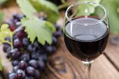 stock photo of grape  - Glass with Red Wine and fresh Grapes on wooden background