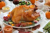 stock photo of fall decorations  - Roasted turkey on a server tray garnished with fresh figs grape kumquat and herbs on fall harvest table - JPG