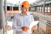 stock photo of supervision  - A foreman with digital tablet supervising the project at the construction - JPG