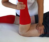 foto of hamstring  - Female sports massage therapist applying a neuromuscular technique to male patient