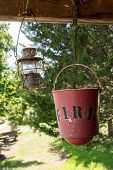 stock photo of rafters  - Old worn fire bucket and oil lamp hanging from rafters of log cabin - JPG