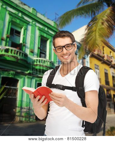 people, travel, tourism and education concept - happy young man with backpack and book travelling over latin american city street background