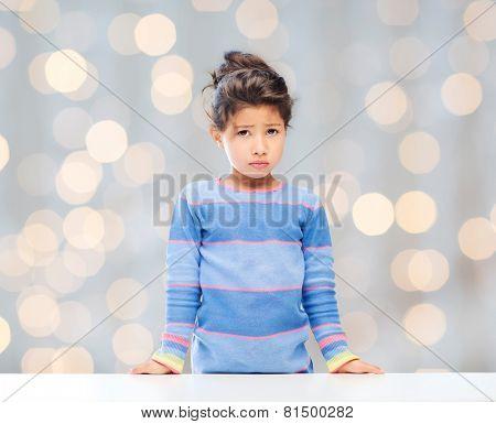 people, childhood and emotions concept - sad little girl over holidays lights background