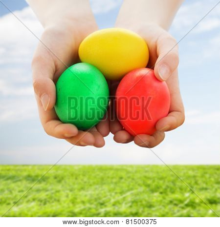 easter, holiday and child concept - close up of kid hands holding colored eggs over blue sky and grass background