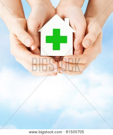 care, help, charity and people concept - close up of hands holding white paper house with green cross sign