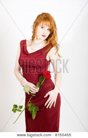 Beautiful elegant woman in a dress with red rose