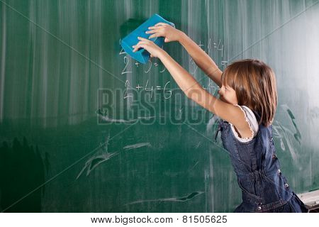 Little Girl In Elementary School Cleaning Board With Spong. Mathematics Task Is Writen On Chalkboard