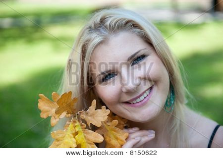 Portrait of pretty autumn woman with yellow leafs outdoors