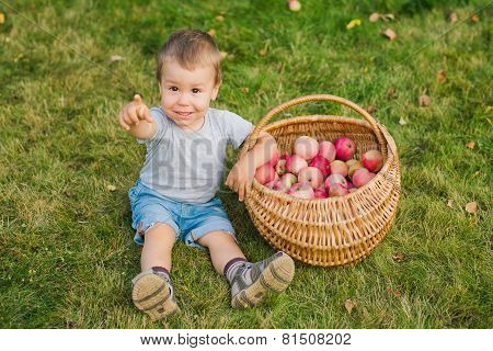 baby with a basket of red apples