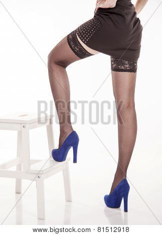 Long Female Legs In Black Stockings And Blue Shoes