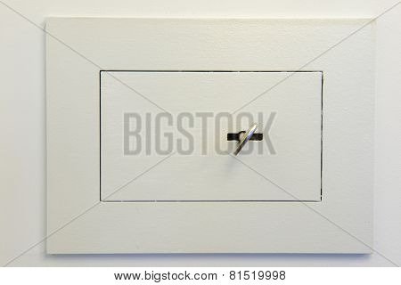 Closed wall mounted safe box with a key.