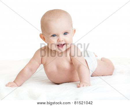 Cute smiling baby lying on white towel in nappy