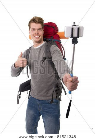 Young Atractive Traveler Backpacker Taking Selfie Photo With Stick Carrying Backpack Ready For Adven