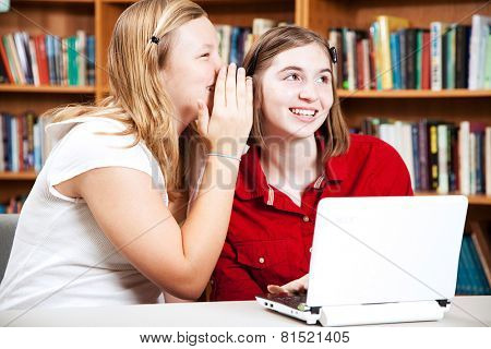 School girls whispering in the library.