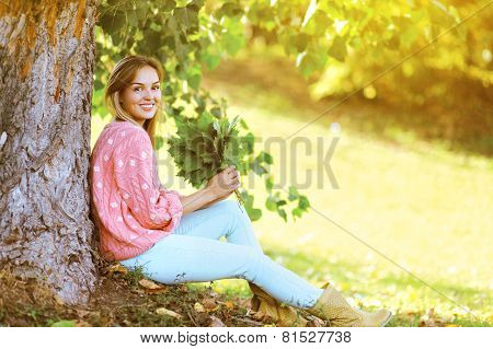 Happy Stylish Pretty Woman With Maple Leafs Outdoors In Warm Sunny Autumn Day In Park