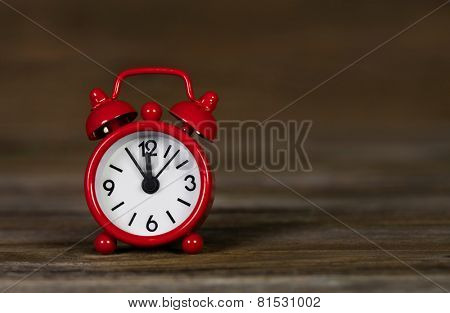 Red alarm clock on wooden old background: time five minutes to 12 o'clock.