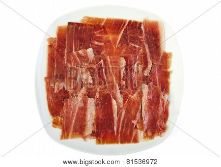 Serrano ham slices on a white dish. Jabugo. Spanish tapa.