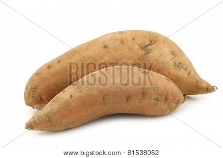 two whole sweet potatoes on a white background