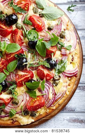 Pizza with cherry tomatoes, red onion and capers (topped with arugula and basil)