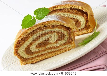 detail of sliced nut roll with sugar, served on the plate with pink linen