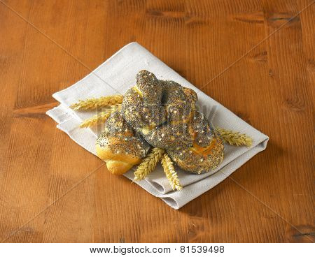 two buns with poppy seeds and wheat ears, on the table with napkin