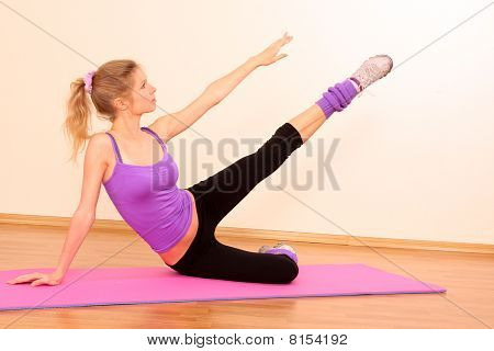 Young Beautiful Fitness Girl Exercising  In The Gym