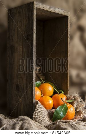 Oranges On Stalk In Rustic Kitchen Setting With Old Wooden Box And Hessian Sack