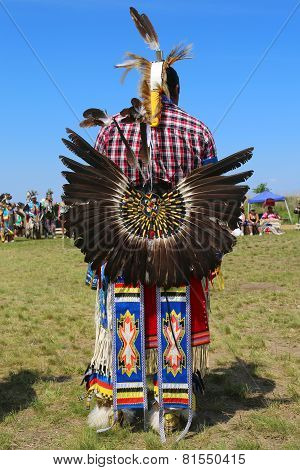 Unidentified male Native American dancer wears traditional Pow Wow dress with Dance Bustle