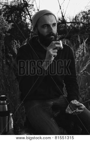 bearded lumberjack with sandwich and tea