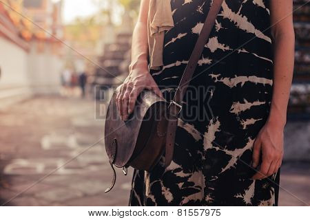 Woman With Handbag In Buddhist Temple
