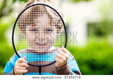 Little Cute Funny Kid Boy Playing Badminton In Domestic Garden