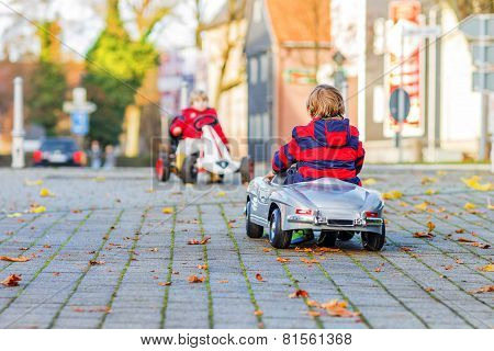 Two Little Kids In Red Jackets Driving Old Vintage And Race Cars