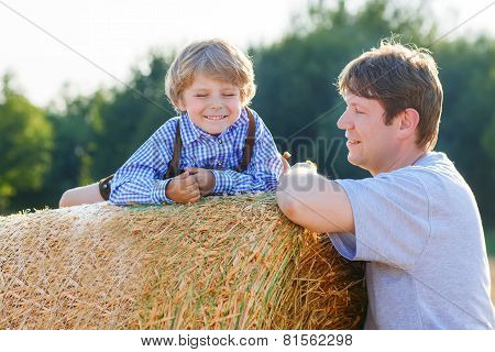 Young Father And His Little Son Having Fun On Yellow Hay Field In Summer