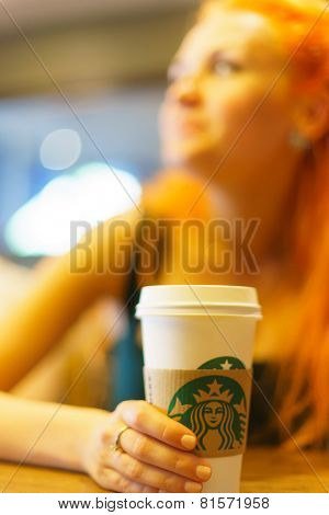 PARIS - SEP 09: young woman in Parisian Sturbucks cafe (focus on cup) on September 09, 2014. Starbucks is the largest coffeehouse company in the world, with more then 23000 stores