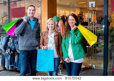 Women And A Man In Front Of Clothes Shop