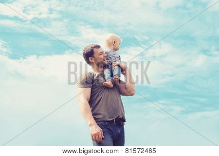 Lifestyle Atmospheric Portrait Happy Father And Son Having Fun Outdoors Against Blue Sky With Clouds