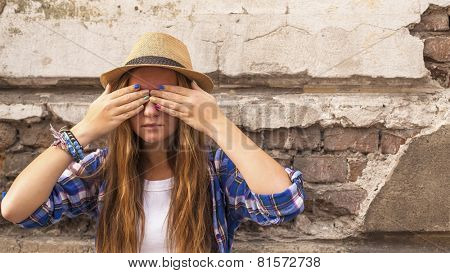 Young cute hipster girl standing in the street old town and closes his eyes his hands with colored nails.