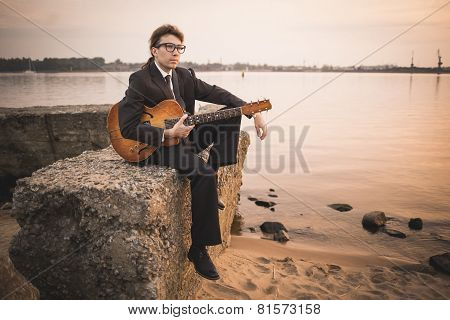 Male musician and his guitar on shore