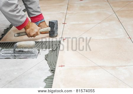 Home improvement, renovation - handyman laying tile, trowel with mortar