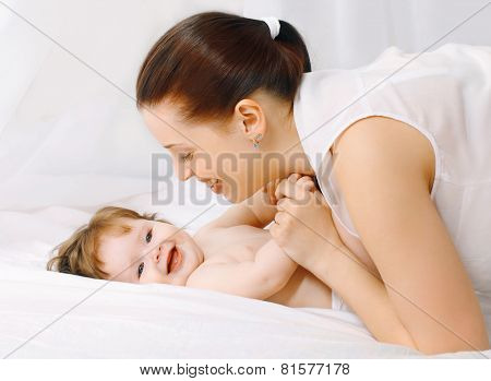Happy Mother And Baby Having Fun In Bed At Home