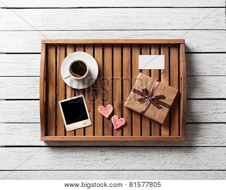 Photo frame and hearts and gift box with cup of coffee on wood.