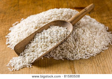 Rustic scoop with basmati rice on a wooden background