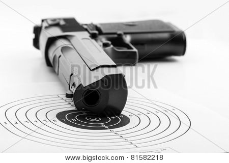 Paper target and pistol on white
