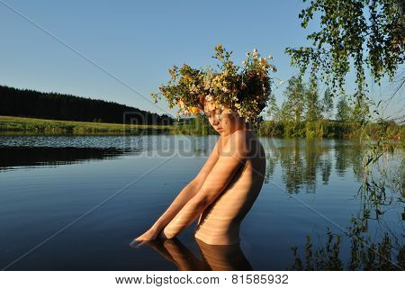 portrait photo of blond naked beautiful model girl standing in the lake looking to camera in summer