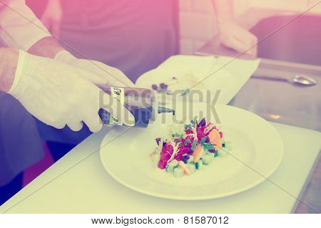 Chef is cooking tuna appetizer, adding balsamic vinegar, toned image, light leak imitation