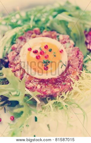 Beef tartare in plate, close-up shot, toned image